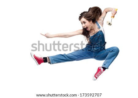 cheerful young caucasian crazy woman jumping and screaming while holding paint roll