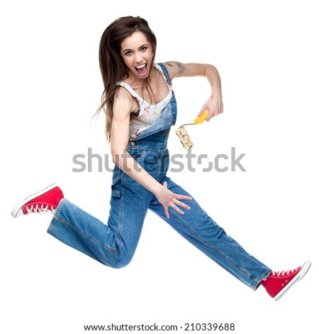 cheerful young caucasian crazy woman jumping and screaming while holding paint roll - stock photo