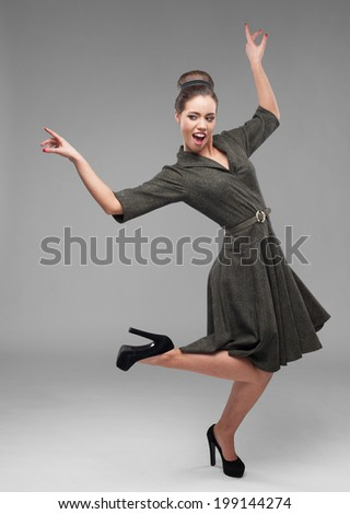 cheerful young caucasian woman in green vintage dress dancing isolated on gray - stock photo