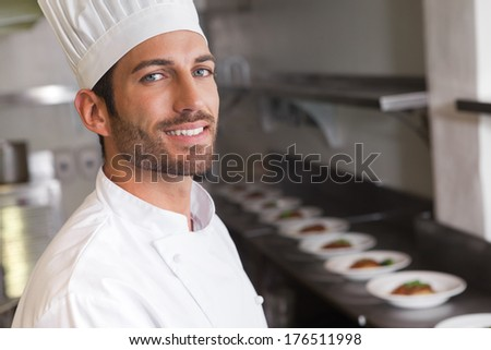 Cheerful young chef smiling at camera in a commercial kitchen - stock photo