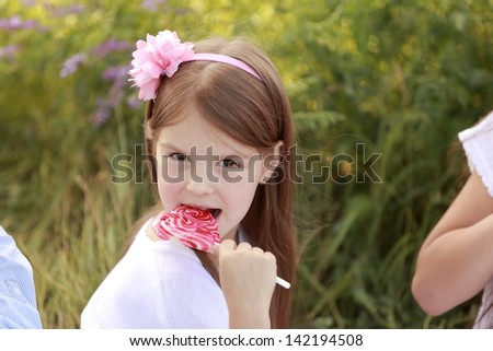 Cheerful young children eat more candy on a stick on a background of green grass outdoors - stock photo