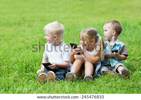 Cheerful young children using smartphones sitting on the grass in the park. Brothers and sister.