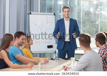 Cheerful young colleagues are taking part in conversation. The businessman is standing and explaining his ideas. The men and women are sitting and writing. They are smiling - stock photo