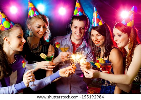 cheerful young company celebrates in a nightclub - stock photo