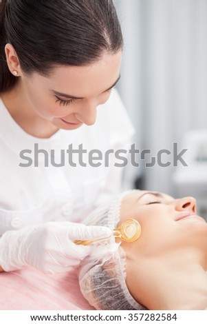 Cheerful young cosmetologist is massaging female face with a roller. She is standing and smiling. The woman is lying with pleasure