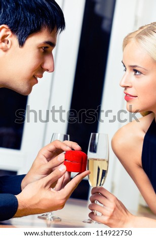 Cheerful young couple and a special man proposal - stock photo