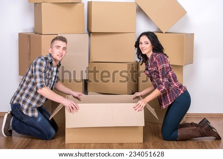 Cheerful young couple are collecting things for the move. - stock photo