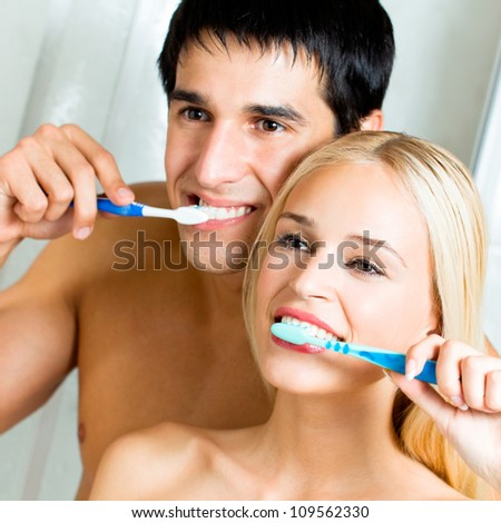 Cheerful young couple cleaning teeth together - stock photo