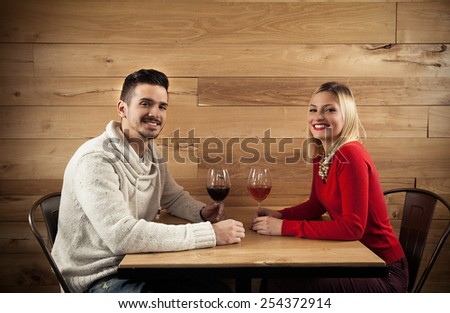 Cheerful young couple drinking wine in a restaurant - stock photo