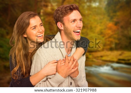 Cheerful young couple embracing against autumn scene - stock photo