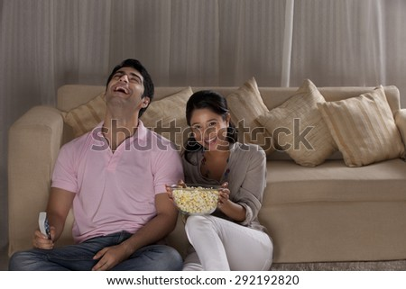 Cheerful young couple enjoying the movie at home - stock photo