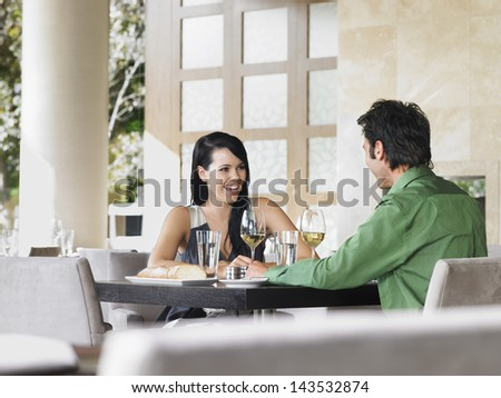 Cheerful young couple enjoying wine at outdoor restaurant - stock photo