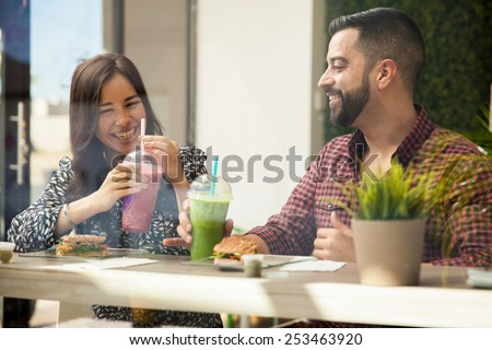 Cheerful young couple having lunch and healthy smoothies at a juice bar - stock photo