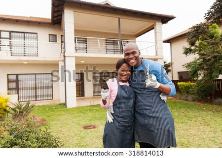 cheerful young couple holding gardening tools standing in front yard