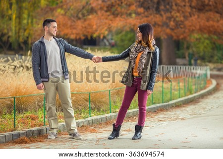 Cheerful young couple holding hands and looking at each other while walking in a park - stock photo