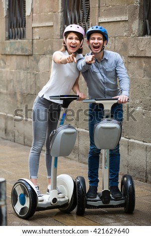 Cheerful young couple in helmets driving segways along the city  - stock photo