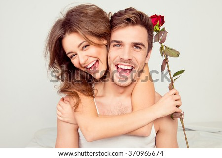 Cheerful young couple in love embracing in the bedroom with rose - stock photo