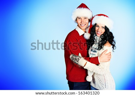 Cheerful young couple in warm winter clothing and Christmas caps.  - stock photo