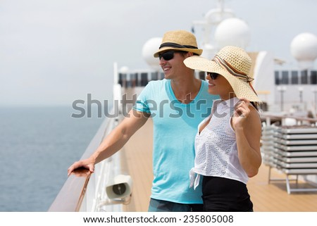 cheerful young couple looking at sea view on cruise ship - stock photo