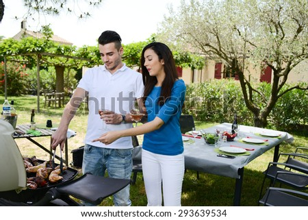 cheerful young couple man and woman cooking barbecue outdoor in a summer garden party - stock photo