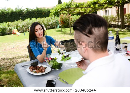 cheerful young couple man and woman having lunch outdoor in a summer barbecue garden party - stock photo