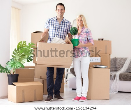 Cheerful young couple moving in their new home  - stock photo