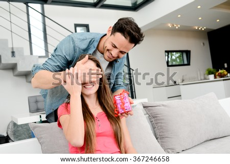 cheerful young couple offering a gift present for birthday or valentines day - stock photo