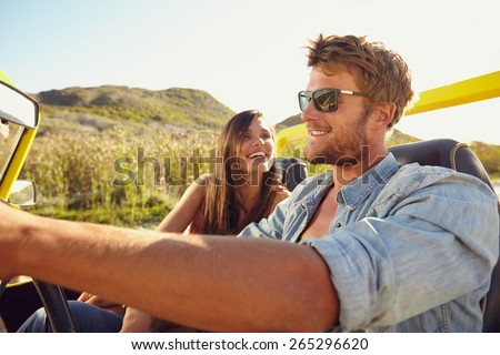 Cheerful young couple on a road trip enjoying the ride. Man driving beach buggy with woman smiling. - stock photo