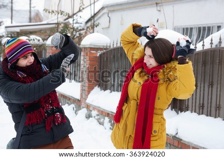 cheerful young couple playing snowballs - stock photo
