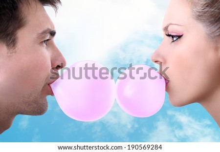 cheerful young couple playing with chewing gum - stock photo