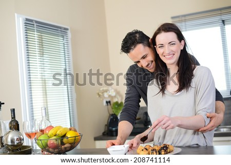 cheerful young couple preparing chocolate dessert in their kitchen at home - stock photo