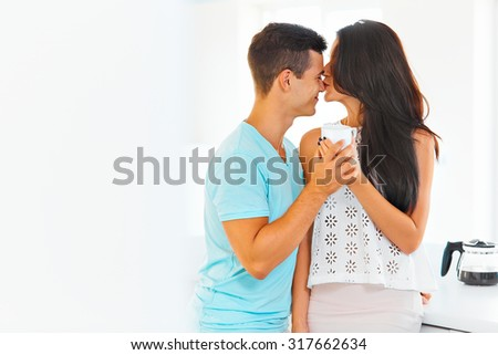 Cheerful young couple relaxing at home, he's laughing as she kisses his nose. - stock photo