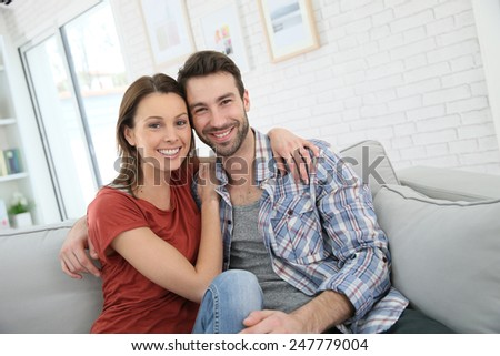 Cheerful young couple relaxing in sofa at home - stock photo