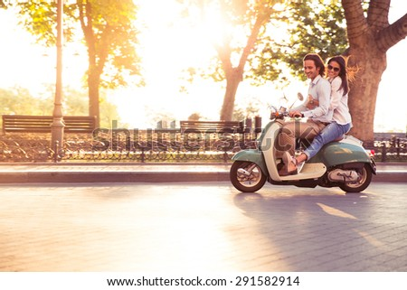 Cheerful young couple riding a scooter and having fun. Sun is shining in the morning - stock photo