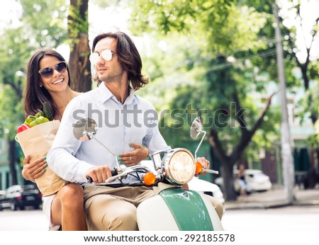 Cheerful young couple riding a scooter while woman holding a shopping bag full of groceries - stock photo