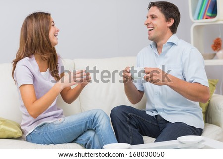 Cheerful young couple sitting on sofa and enjoying their tea at home - stock photo