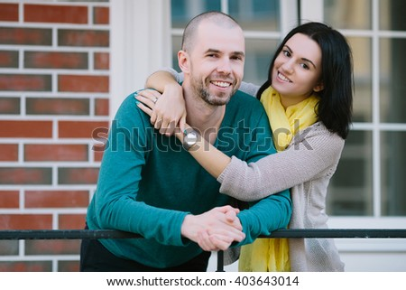Cheerful young couple standing in front of new house look at the camera moving purchase of new habitation - stock photo