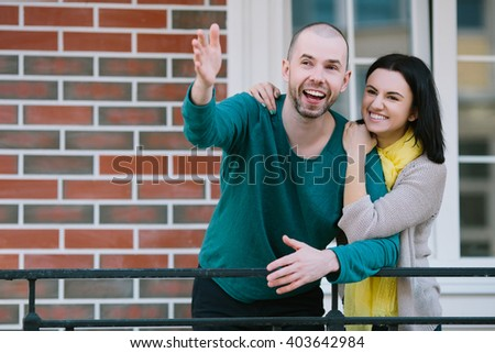 Cheerful young couple standing in front of new house moving purchase of new habitation - stock photo