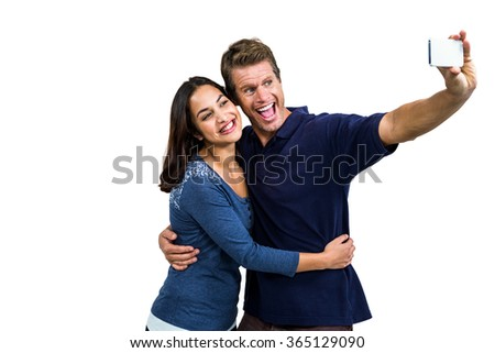 Cheerful young couple taking selfie against white background - stock photo