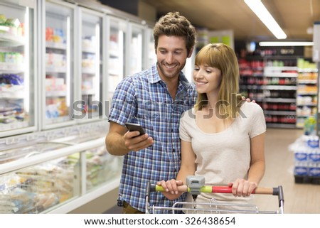 Cheerful young couple using cell phone in supermarket - stock photo