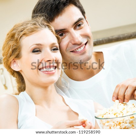Cheerful young couple watching TV together - stock photo