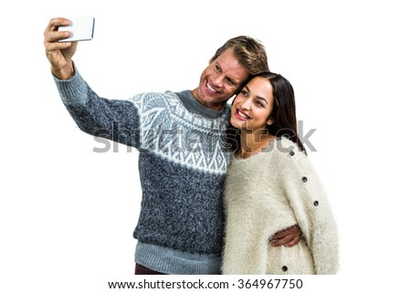 Cheerful young couple wearing warm clothing taking selfie against white background - stock photo