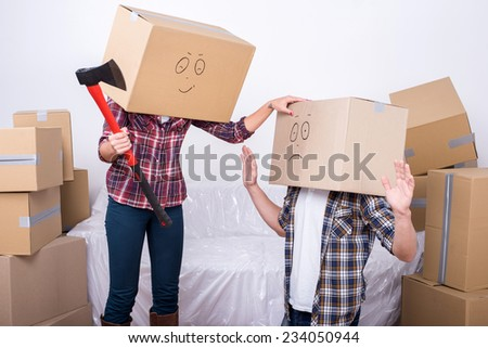 Cheerful young couple with cardboard boxes on their heads. A woman holds an ax. - stock photo