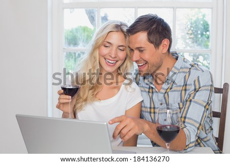Cheerful young couple with wine glasses using laptop at home