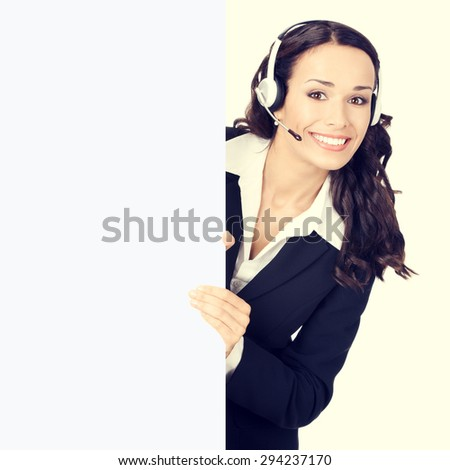 Cheerful young customer support phone operator or businesswoman in headset showing blank signboard - stock photo