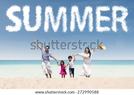 Cheerful young family enjoy holiday on the tropical seaside under a summer's cloud - stock photo