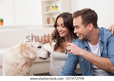 Cheerful young family is moving in new apartment. They are sitting on flooring with joy. The man is showing a key to a dog. The married couple is embracing and smiling - stock photo