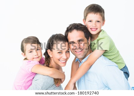 Cheerful young family looking at camera together on white background - stock photo