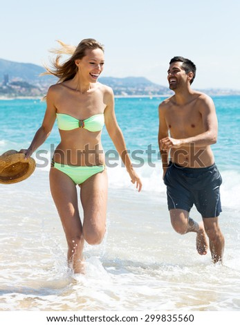Cheerful young family running on the shore. Focus on the woman - stock photo