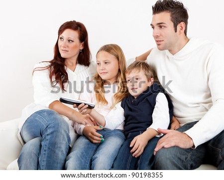 Cheerful young family watching TV together at home - stock photo
